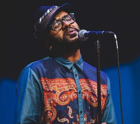Benny Dayal, wearing a quirky bowler hats, Aztec print shirts and trousers in pop colours